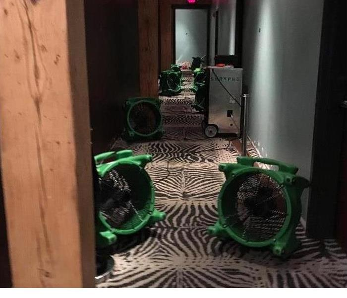 Hallway with water damaged carpet and SERVPRO equipment